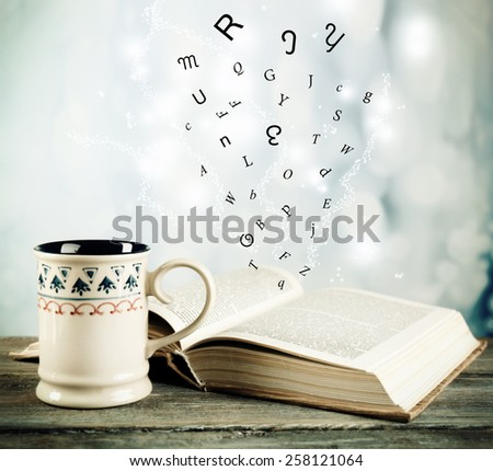 Open book with flying letters on table on bright background - stock photo