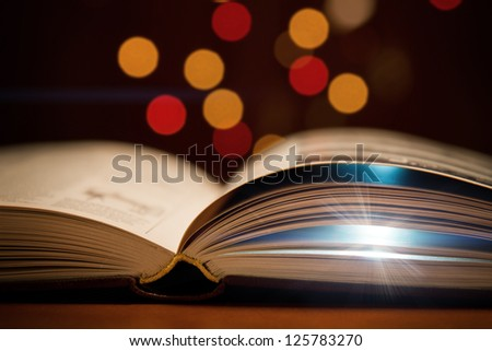 Open book with light going from within - stock photo