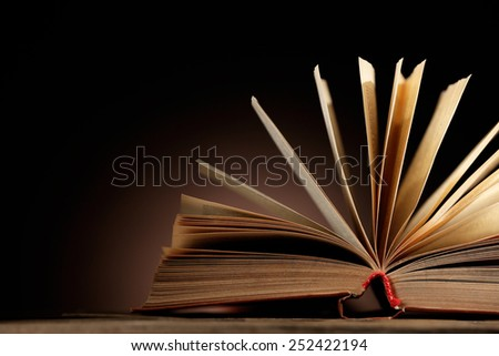 Open book with light over dark background