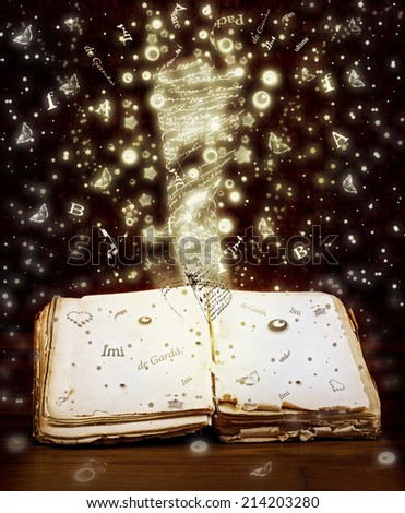 Open book with magic light and magic letters and drawings - stock photo