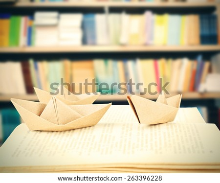 Open book with paper ships on bookshelves background - stock photo