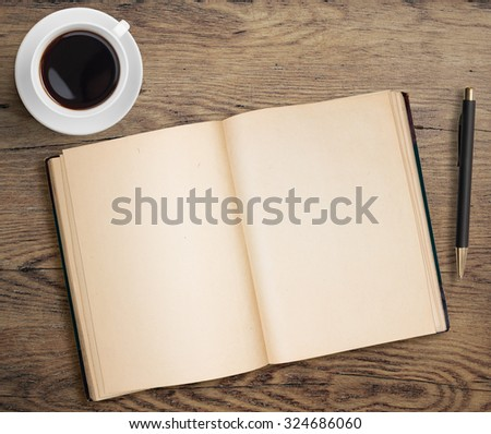 Open book with pen and coffee cup on old wooden table - stock photo