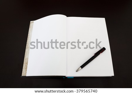 Open book with pen on dark wood desk. - stock photo