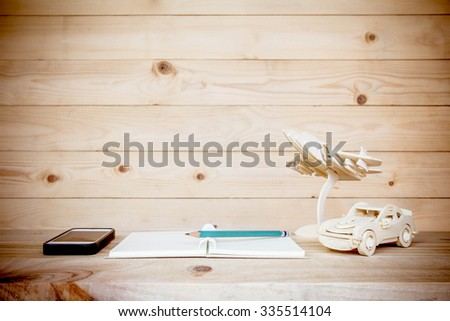 Open book with pencil and Mobile phone on wooden table, home decoration concept. - stock photo