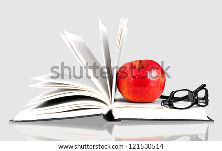 Open book with rad apple and black glasses on grey background - stock photo