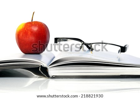 Open book with red apple and black glasses - stock photo
