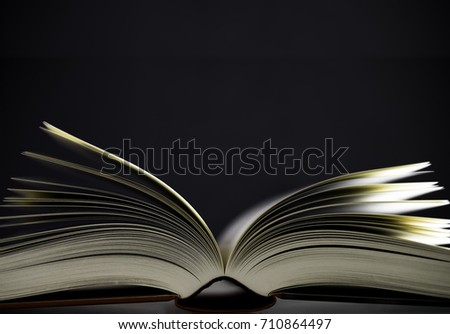 Open book with red cover and shallow depth of field on black background