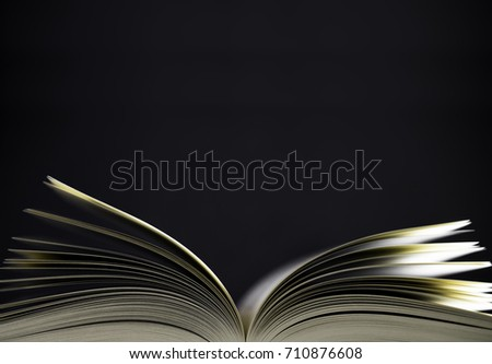 Open book with shallow depth of field on black background