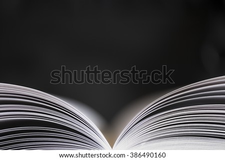 Open book with shallow depth of field with black background