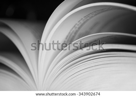 Open book with shallow depth of field with black background, black and white photo - stock photo
