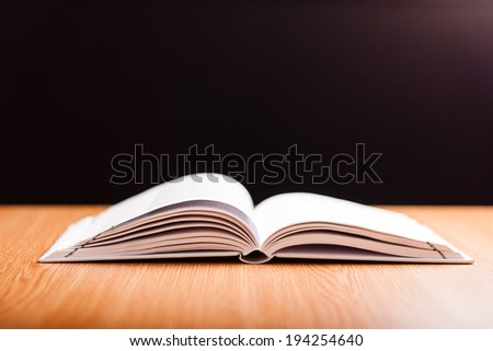 open book with white pages on wooden table