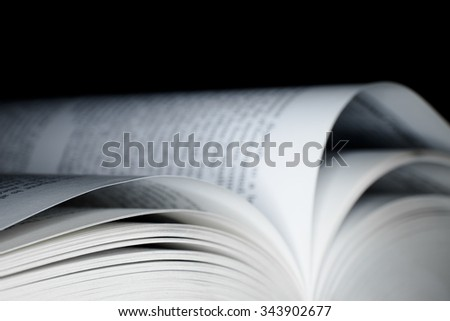 Open book with with shallow depth of field with black background