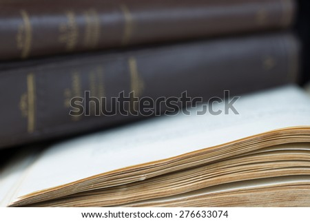 Open book with yellowed pages close-up on background old book covered in brown leather-bound