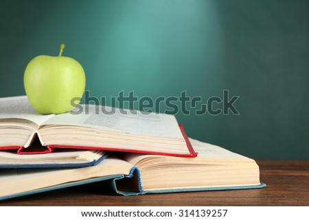 Open books and green apple on desk on green chalkboard background