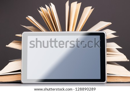 Open books and modern tablet computer, concept of evolution
