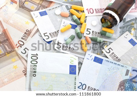 Open bottle of pills and capsules on top of money. - stock photo