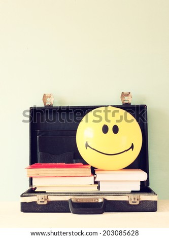 open briefcase books and beach ball. concept for travel or vacation. - stock photo