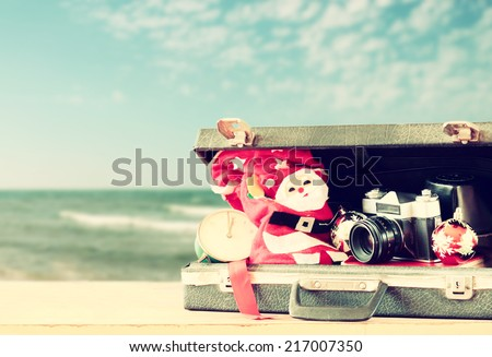 open briefcase with christmas decorations and camera in front of beach view. christmas holiday concept.  - stock photo