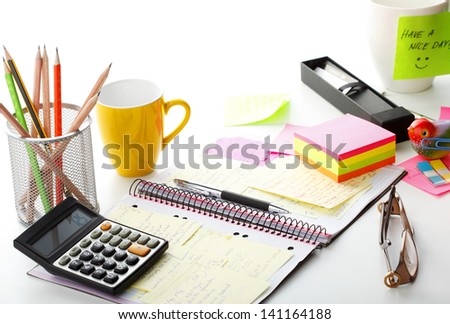 "Open business diary with pink and yellow ""Post It"" notes, calculator and with office supplies. Shallow focus. - stock photo"
