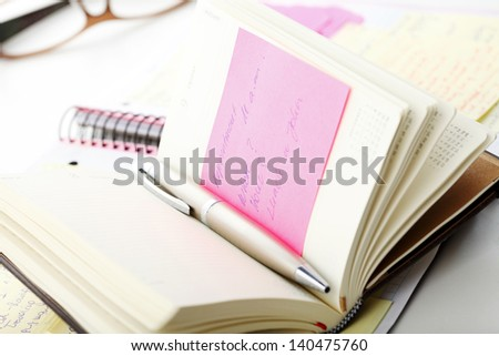 "Open business diary with ""Post It"" notes and pen on office desk - stock photo"