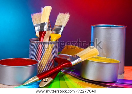 Open cans with bright colors, brushes and palette on wooden table