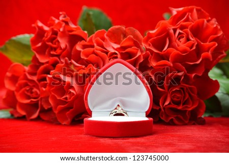 Open case with a ring around the bouquet of roses on a red background - stock photo