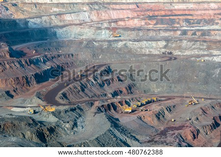 open cast mine extracting iron ore with heavy trucks, excavators, diggers and locomotives