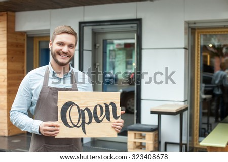 Open. Cheerful male owner of coffee shop is standing outdoors. He is holding placard and inviting everybody to come in. The man is looking at camera and smiling - stock photo