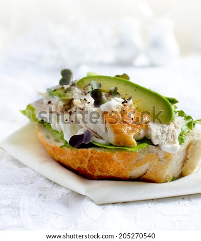 Open chicken and avocado sandwich with garnish and dressing against a light background. Copy space. - stock photo