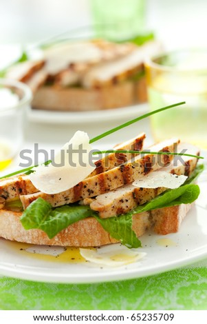 Open chicken Caesar sandwich on the white plate - stock photo