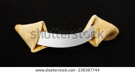 Open chinese fortune cookie isolated on the black background - stock photo