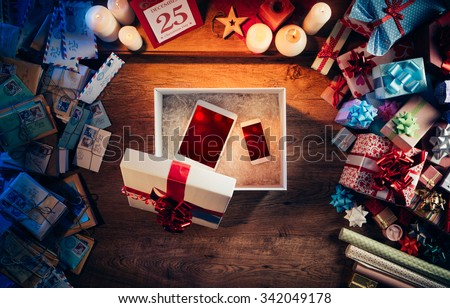 Open Christmas gift box with a tablet and a smart phone inside, presents and letters all around, top view - stock photo