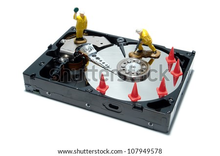 Open computer hard disc drive hardware component with miniature toy figurines work crew over white as concept illustration for routine registry repair and defragmentation (1 in a series of 6)