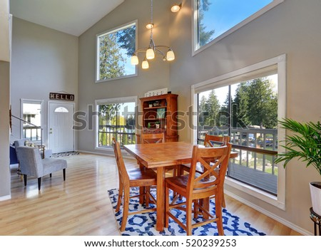 Open concept dining room with rustic table set , high ceiling and amazing window view. Northwest, USA