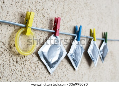 open condom and sealed condoms on colorful clothespins. selective focus image - stock photo