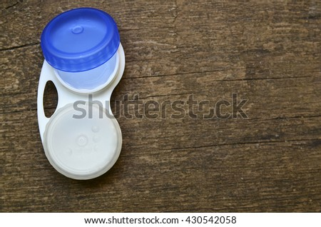 Open contact lens case on wooden  background with space for text. - stock photo