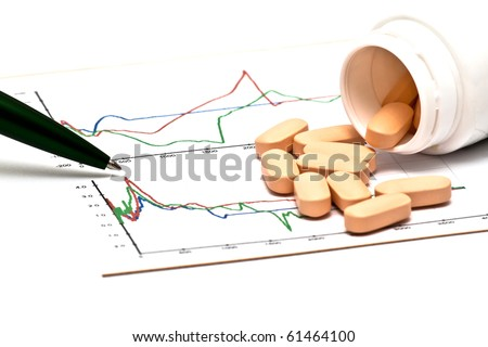 Open container with pills and pen on a chart - stock photo