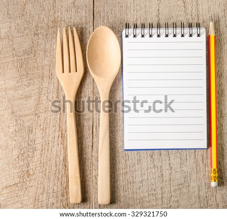 Open cookbook and kitchenware on wooden table background - stock photo