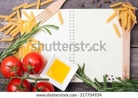 Open cookbook, spoon with penne pasta, tomatoes, rosemary and olive oil in a bowl on wooden background. Ingredients for cooking. Open blank recipe book. Top view - stock photo