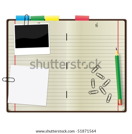 Open copybook with a green pencil, photograph and paper clips.