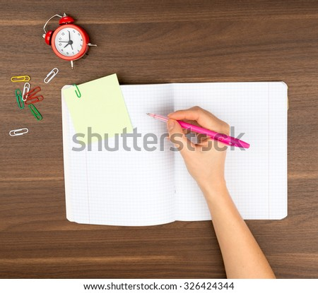 Open copybook with sticker on wooden table - stock photo