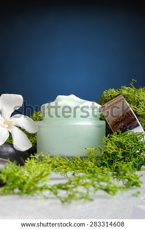 Open cream jar algae. Flowers, black stones and seaweed decoration. Blue background. Front and vertical view - stock photo