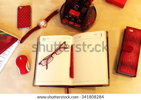Open daily planner, computer, cell phone, business card holder, sunglasses, watches and stationery in red style - stock photo