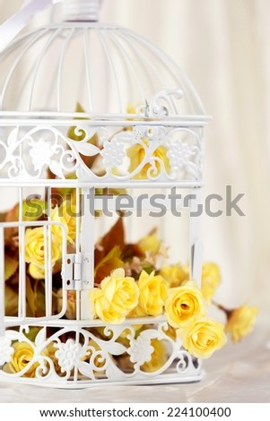Open decorative cage with yellow flowers, with champagne color satin in the background. - stock photo