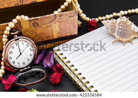 Open diary and vintage pocket watch with decorate on black background. - stock photo