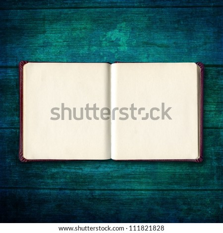 open diary or photo album book on old wooden table - stock photo