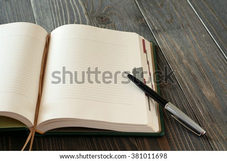 Open diary with blank pages and pen closeup on a dark wooden table