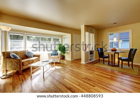 Open dining room with hardwood floor connected to dining room with teo black leather chairs