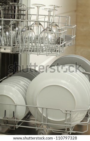 Open dishwasher full of plates, close up - stock photo