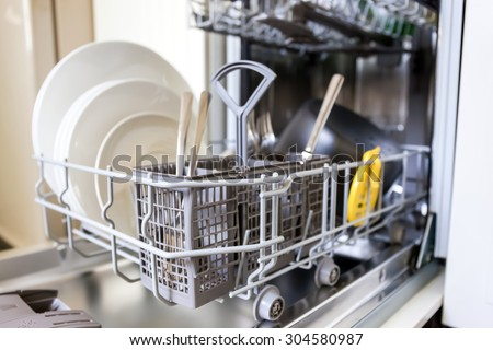 Open dishwasher with clean glass and dishes, selective focus